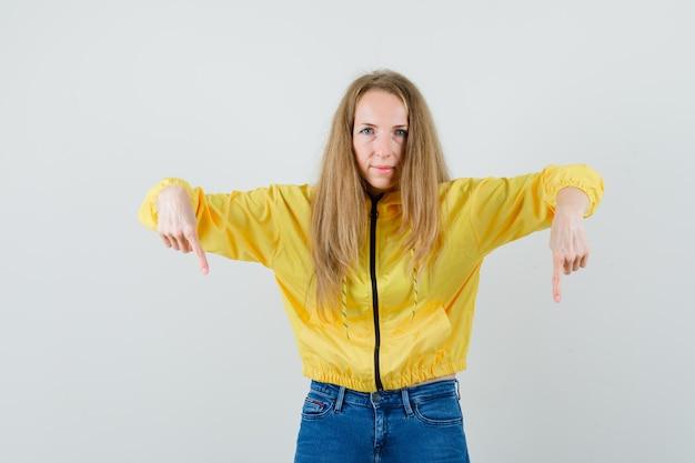 Jonge vrouw in geel bomberjack en blauwe jean die naar beneden wijst en ernstig, vooraanzicht kijkt.