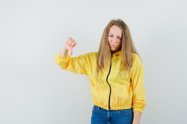 Jonge vrouw in geel bomberjack en blauwe jean met duim naar beneden en op zoek naar ontevreden, vooraanzicht.
