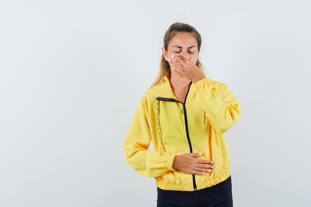 Jonge vrouw in geel bomberjack en zwarte broek neus knijpen vanwege slechte geur terwijl hand op buik en uitgeput op zoek