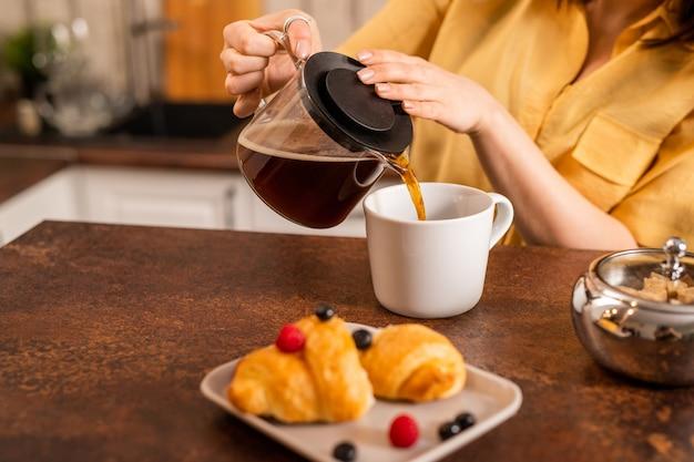 Jonge vrouw in geel overhemd aan tafel zitten en verse kruidenthee in beker gieten terwijl verse croissant als ontbijt gaat hebben