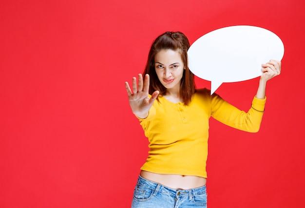 Jonge vrouw in geel overhemd die een ovale inforaad houdt en iemand tegenhoudt