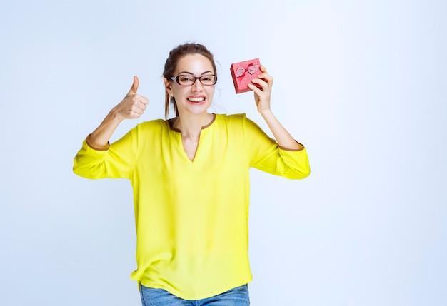 Jonge vrouw in geel overhemd die een rode giftdoos houdt en het teken van de plezierhand toont