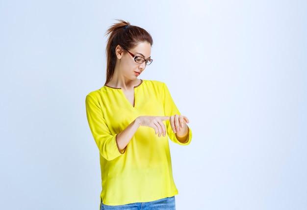 Jonge vrouw in geel overhemd die haar tijd controleert