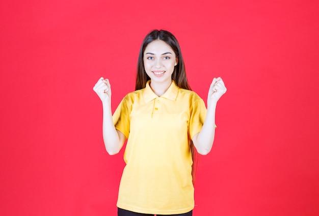 Jonge vrouw in geel overhemd die zich op rode muur bevindt en positief handteken toont