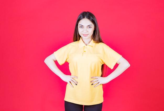 Jonge vrouw in geel overhemd die zich op rode muur bevindt