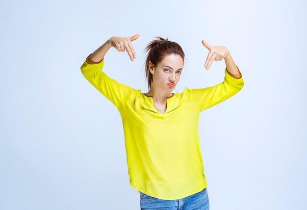 Jonge vrouw in geel overhemd wijzend op zichzelf