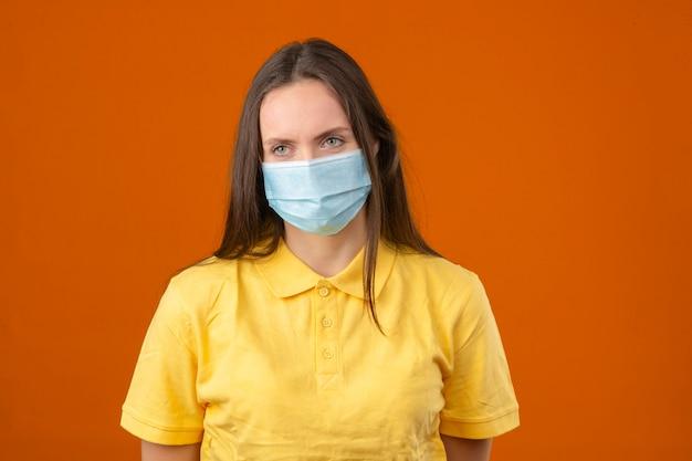 Jonge vrouw in geel poloshirt en medisch beschermend masker dat zich op oranje achtergrond bevindt