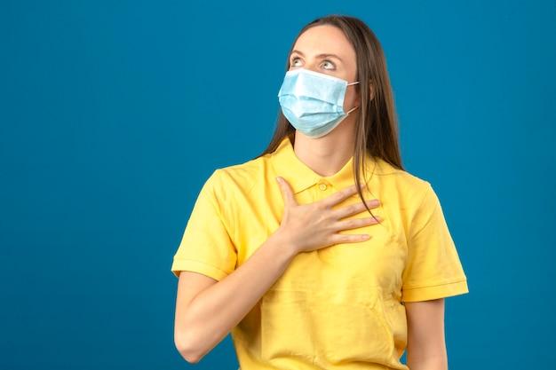 Jonge vrouw in geel poloshirt en medisch beschermend masker die omhooggaand en wat betreft haar borst op blauw geïsoleerde achtergrond kijken
