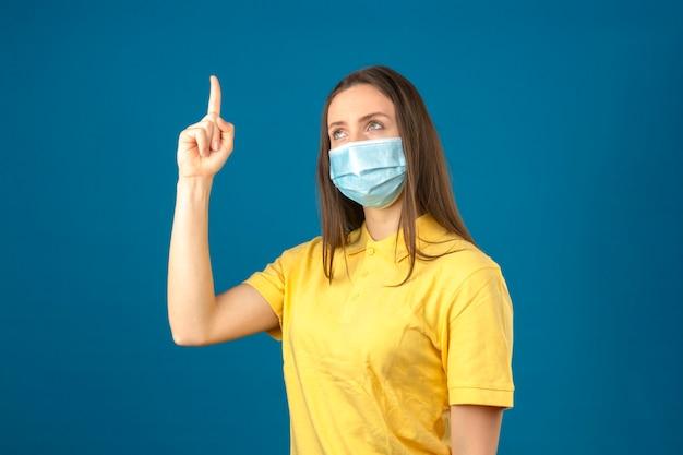 Jonge vrouw in geel poloshirt en medisch beschermend masker die vinger op geïsoleerde blauwe achtergrond benadrukken