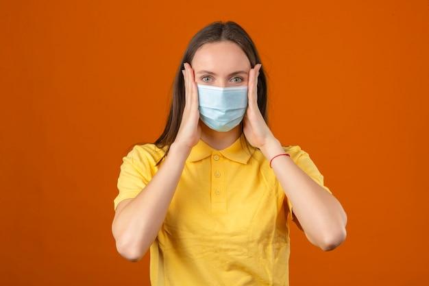 Jonge vrouw in geel poloshirt en medisch beschermend masker wat betreft haar gezicht dat camera op oranje achtergrond bekijkt