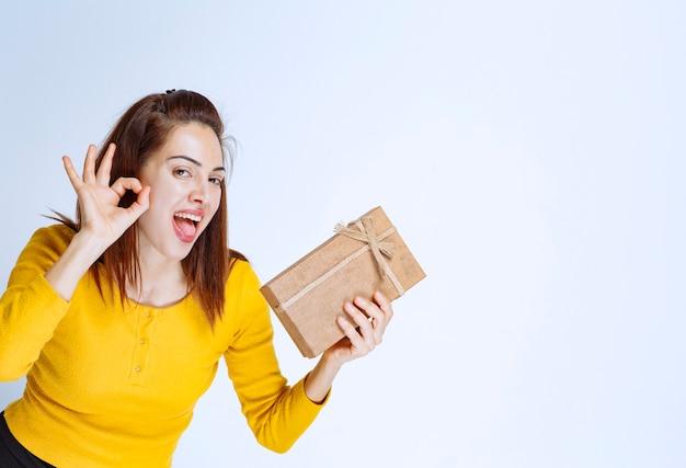 Jonge vrouw in geel shirt die een kartonnen geschenkdoos vasthoudt en een positief handteken toont