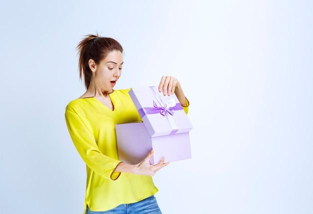 Jonge vrouw in geel shirt die een paarse geschenkdoos opent met verrassing