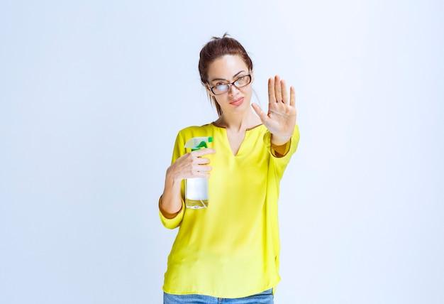 Jonge vrouw in geel shirt die een reinigingsspray vasthoudt en weigert met iemand te delen