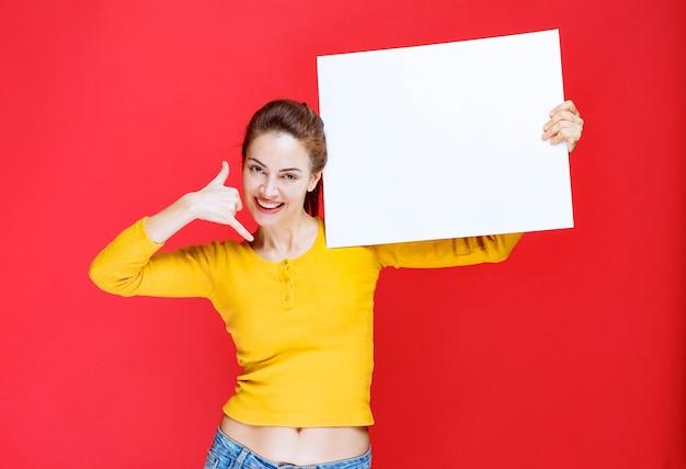 Jonge vrouw in geel shirt die een vierkant infobord vasthoudt en om een telefoontje vraagt