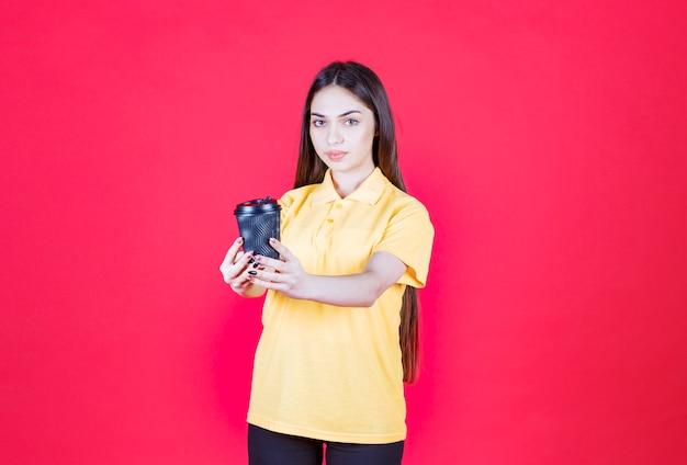 Jonge vrouw in geel shirt die een zwarte wegwerpkoffiekop vasthoudt en haar partner uitnodigt om mee te delen