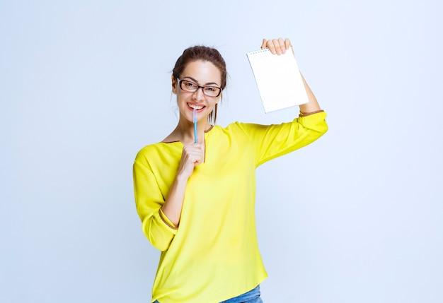 Jonge vrouw in geel shirt die haar examenblad vasthoudt en denkt terwijl ze een pen vasthoudt