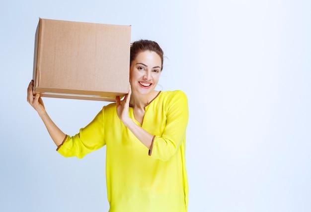 Jonge vrouw in geel shirt die haar kartonnen laaddoos vasthoudt en zich gelukkig voelt