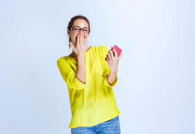 Jonge vrouw in geel shirt die haar rode geschenkdoos laat zien en er verrast uitziet