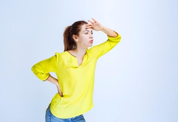 Jonge vrouw in geel shirt die hand op het voorhoofd legt en vooruit kijkt