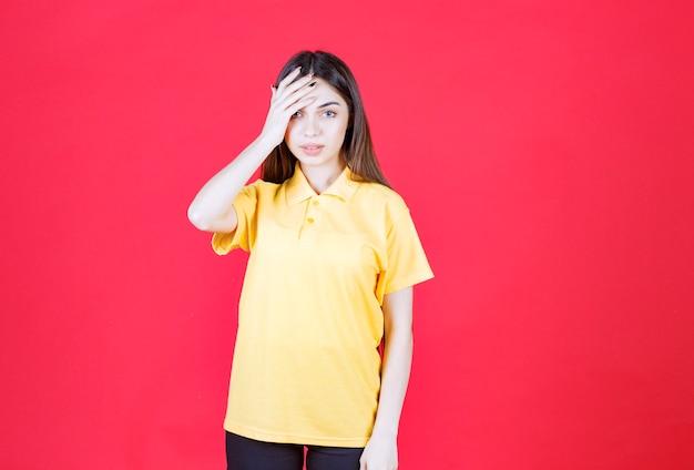 Jonge vrouw in geel shirt die op de rode muur staat en er moe en slaperig uitziet