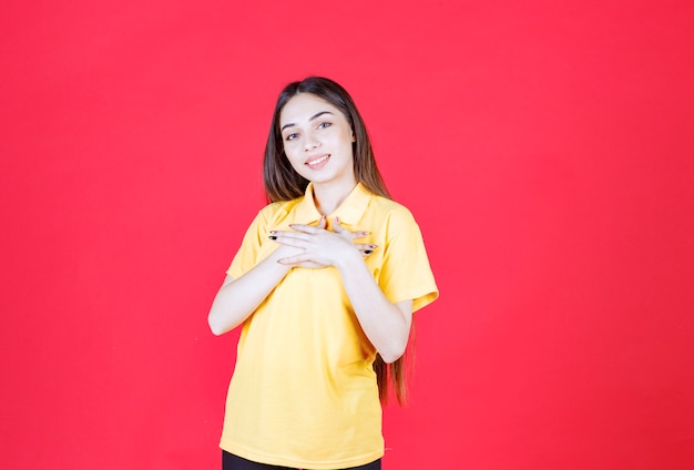 Jonge vrouw in geel shirt die op de rode muur staat en naar zichzelf wijst