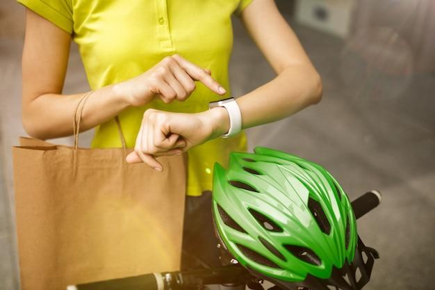 Jonge vrouw in geel shirt die pakket aflevert met gadgets om de bestelling in de straat van de stad te volgen. koerier die online app gebruikt voor het ontvangen van betaling en het volgen van het verzendadres. moderne technologieën.