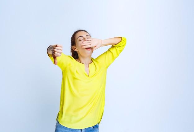Jonge vrouw in geel shirt met duim omlaag