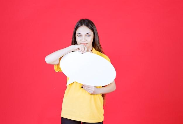 Jonge vrouw in geel shirt met een ovale infobord