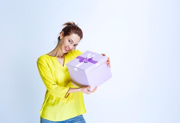 Jonge vrouw in geel shirt met een paarse geschenkdoos en ziet er gelukkig uit