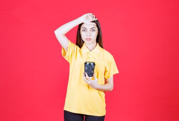 Jonge vrouw in geel shirt met een zwarte wegwerpkoffiekop en ziet er moe en slaperig uit