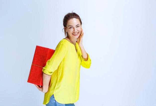 Jonge vrouw in geel shirt verbergt een rode geschenkdoos achter zichzelf