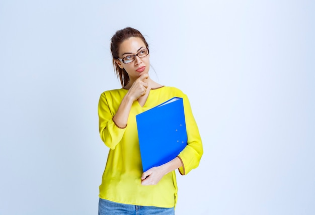 Jonge vrouw in geel shirt ziet er attent en dromerig uit