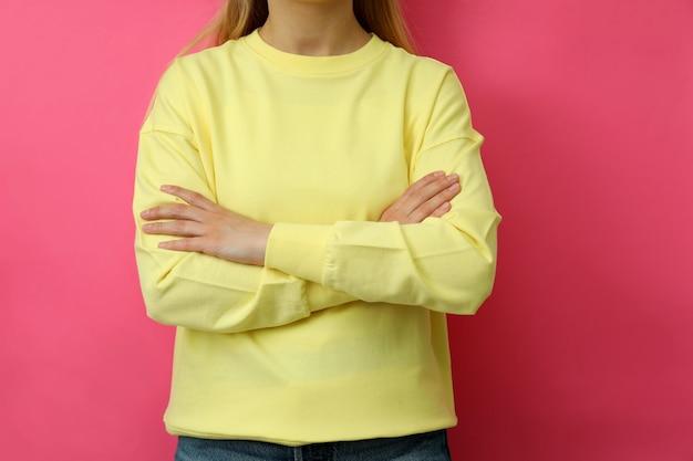 Jonge vrouw in geel sweatshirt tegen roze achtergrond