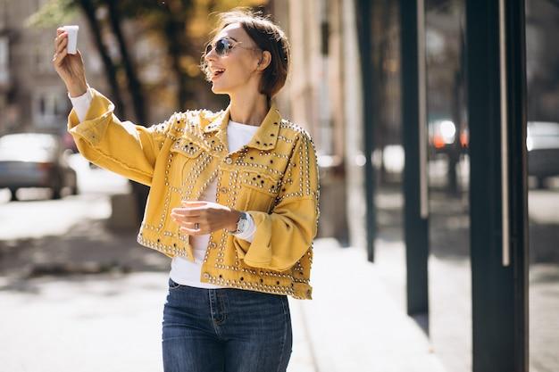 Jonge vrouw in gele jas met behulp van telefoon buiten in de straat