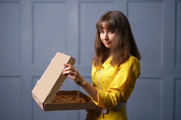 Jonge vrouw in gele jumpsuit die pizza levert. het concept van kleine bedrijven