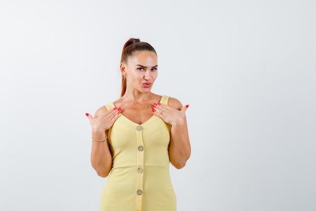 Jonge vrouw in gele jurk hand in hand op de borst en op zoek beschaamd, vooraanzicht.