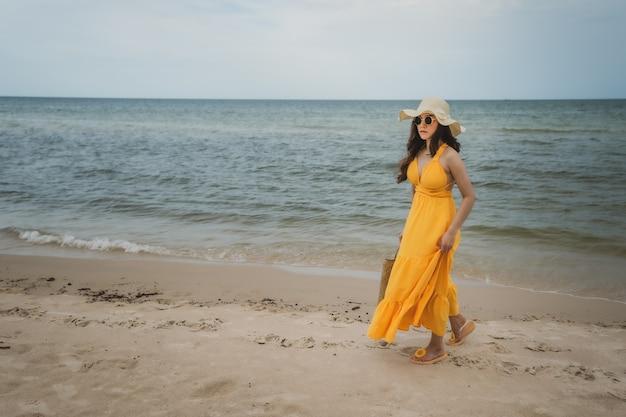 Jonge vrouw in gele jurk wandelen op het strand