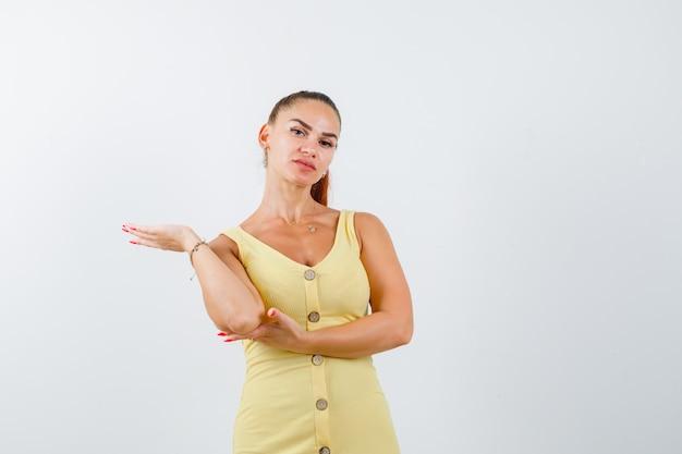 Jonge vrouw in gele kleding die palm opzij spreidt en ernstig, vooraanzicht kijkt.