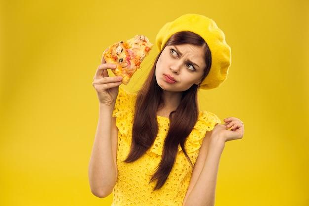Jonge vrouw in gele kleren eet pizza