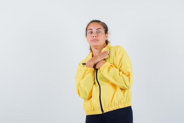 Jonge vrouw in gele regenjas die hand op haar borst houdt en angstig kijkt
