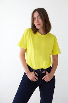 Jonge vrouw in gele t-shirt witte achtergrond