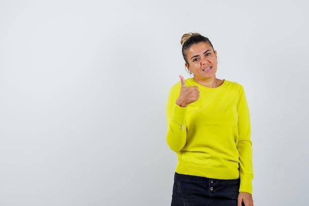 Jonge vrouw in gele trui en zwarte broek die duim toont en er gelukkig uitziet