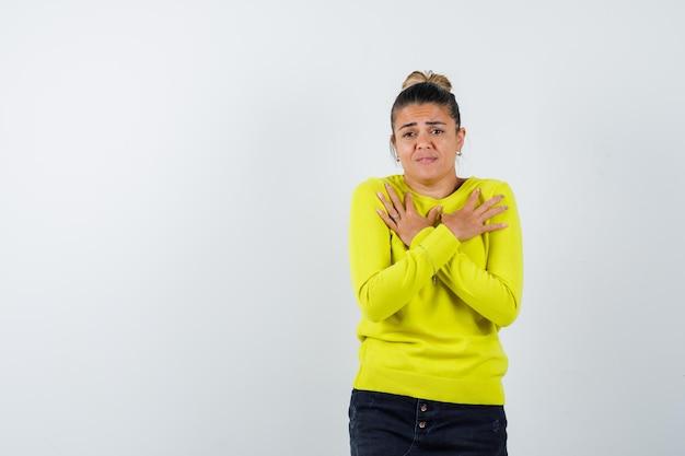 Jonge vrouw in gele trui en zwarte broek die een beperkingsgebaar toont en er serieus uitziet