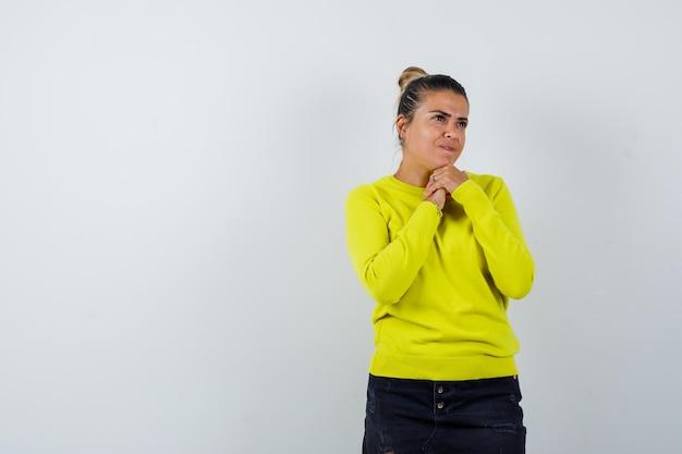 Jonge vrouw in gele trui en zwarte broek die handen omklemt, aan iets denkt en peinzend kijkt
