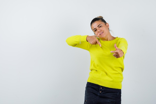 Jonge vrouw in gele trui en zwarte broek die met wijsvingers naar de camera wijst en er gelukkig uitziet