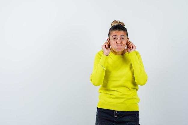 Jonge vrouw in gele trui en zwarte broek die oren uitrekt met vingers, wangen puffend en er geamuseerd uitziet