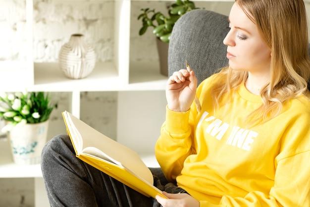 Jonge vrouw in gele trui grijze broek ontspannen op stoel thuis schrijven op een notitieblok
