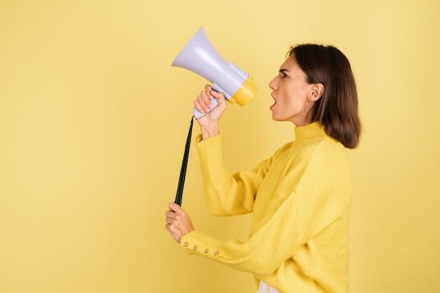 Jonge vrouw in gele warme trui met megafoonluidspreker die naar links schreeuwt op lege ruimte