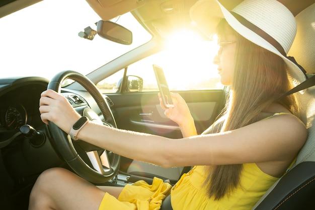 Jonge vrouw in gele zomerjurk met behulp van mobiele telefoon