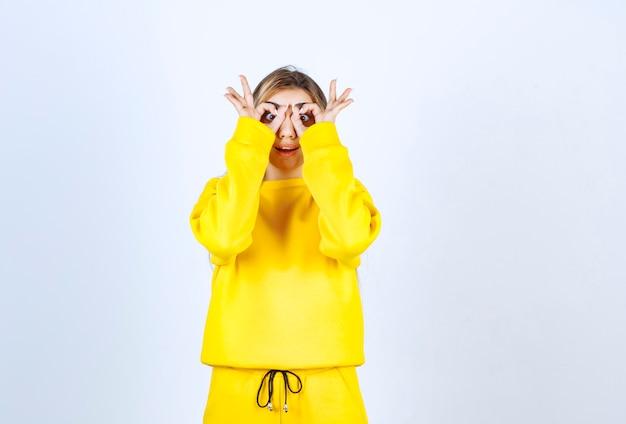 Jonge vrouw in gele zweetbroek en hoodie die verrekijker ogen maakt
